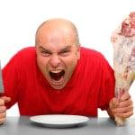 Mand med kødstykke og kniv