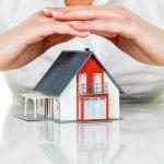 Beskyttende hænder over et hus - forsikring