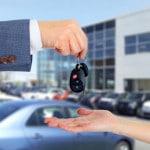 Bilnøgler skifter hænder foran en masse biler - køb af bil