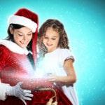 Kvinde i julemandskostume ser på en pakke til en lille pige