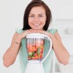 Kvinde i køkkenet med blender fuld af grøntsager og frugt