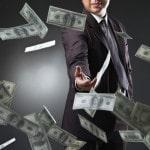 Mand i jakkesæt kaster pengesedler i grams