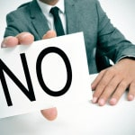 Mand i jakkesæt viser et skilt med teksten No - nej