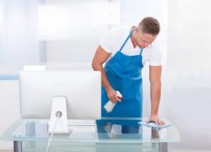 Professionel rengøringsassistent er ved at tørre et glasbord af