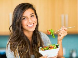 Smuk ung kvinde spiser salat med grøntsager