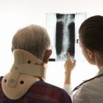 Mand med halskrave ser på røntgenfotos - piskesmæld