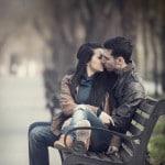 Par kysser på en bænk i parken - romantik
