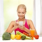 Ung kvinde tæller kalorier foran en masse sunde grøntsager