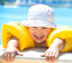 Lille dreng med gule svømmevinger i swimming pool
