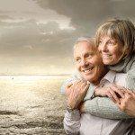 Midaldrende ægtepar ser ud over havet