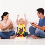 Forældre leger med klodser med barn