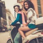 To piger på en cremefarvet scooter
