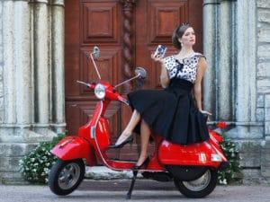 Und kvinde i sort kjole på rød scooter